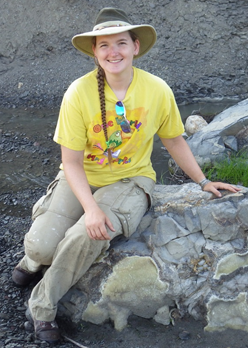 Becky sitting on rock in the little Pembina river