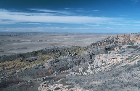 The southwest edge of Black Butte, Slope County. Note that numerous sandstone blocks litter this slope. These blocks broke from the caprock and toppled and slid  								down the slope. Snow Cave was located in this general area.