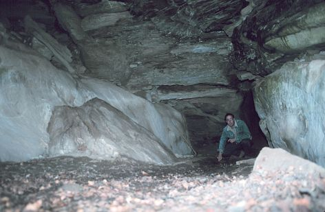 The inside of this, the largest Ice Cave, measures approximately 30 feet long, 10 feet wide, and 8 feet high. This cave is the space left between four  								or five blocks of sandstone. I am pointing to ice on the floor of the cave. Photograph taken near the entrance