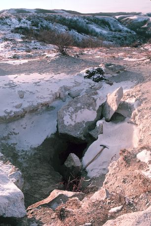 Medicine Hole in winter. This photograph was taken in 1985. In more recent years the rocks that were placed over part of the entrance to discourage cavers have been removed.  								Spelunker Jerry Forney noted while exploring Medicine Hole that there was a pile of pebbles on the floor of the cave below the opening which had formed from people over the years dropping pebbles  								to test the depth of the 70 foot-deep crack.